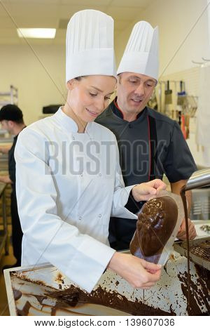 commis chef prepares chocolate with chef checking