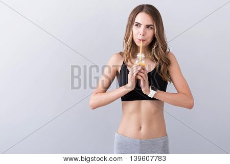 Source of vitamins. Pleasant beautiful delighted woman holding bottle and drinking juice while expressing gladness