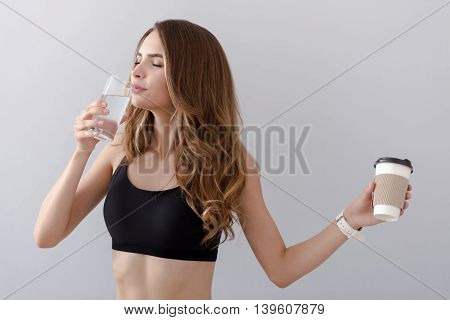 Best choice. Delighted beautiful smiling woman drinking water and closing her eyes in delight while holding coffee