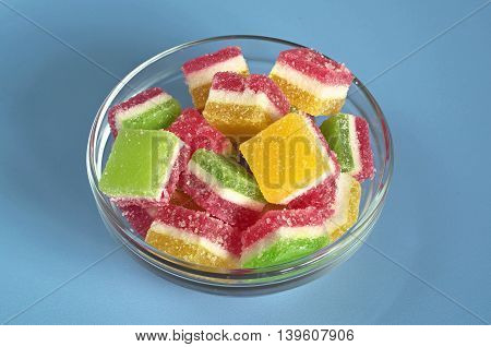 Candied fruit jelly in glass bowl on blue table