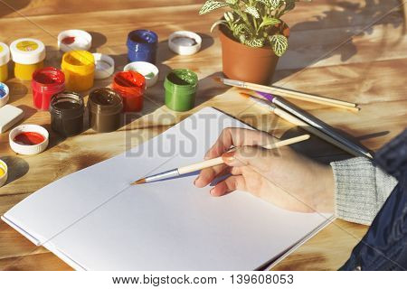 The artist's hand holds the brush and empty album paint pencils and flower on wooden background.
