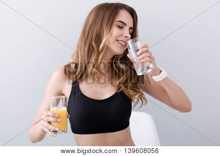 Revel in healthy life. Pleasant delighted woman sitting in the chair and drinking water while holding glass of orange juice