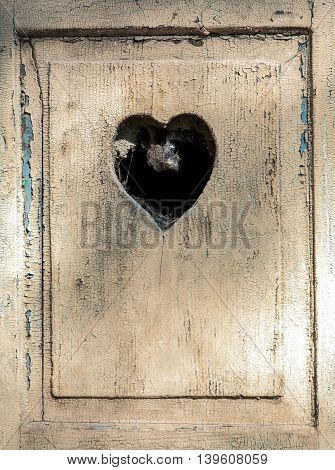 old wooden door in meran Tirol Italy with a carved romantic heart