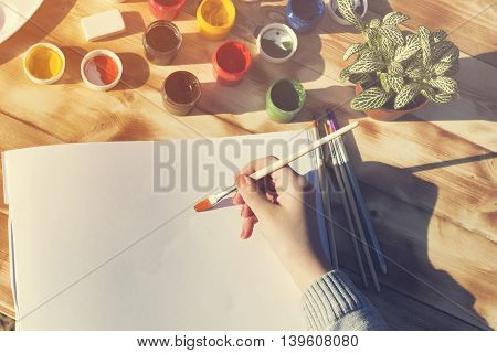 The artist's hand holds the brush and empty album paint pencils and flower on wooden background. The view from the top