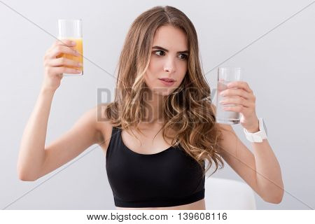 Between two options. Pleasant beautiful puzzled woman holding glass of water and juice while standing isolated on grey background