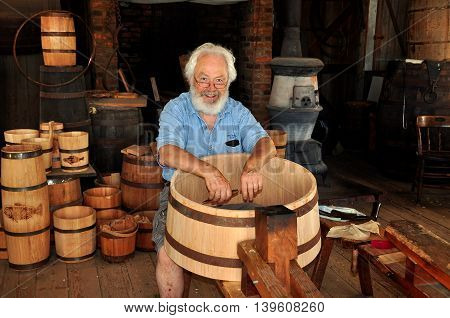 Mystic Connecticut- July 11 2015: Cooper at work making a wooden barrel in the Cooperage Shop at Mystic Seaport