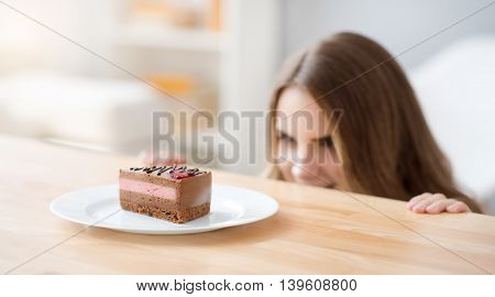 Bomb of calories. Close up of plate with piece of cake lying on the table while positive beautiful woman looking at it