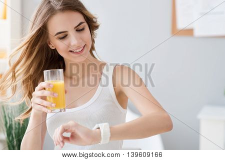 Nice rhythm of life. Pleasant cheerful beautiful woman looking at her wrist watch and drinking orange juice while expressing joy