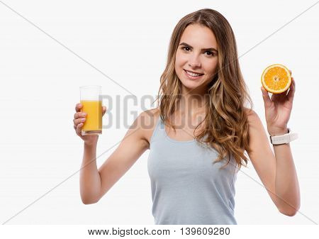 Brighten up your routine. Cheerful delighted beautiful woman holding orange and glass of juice while standing isolated on white background