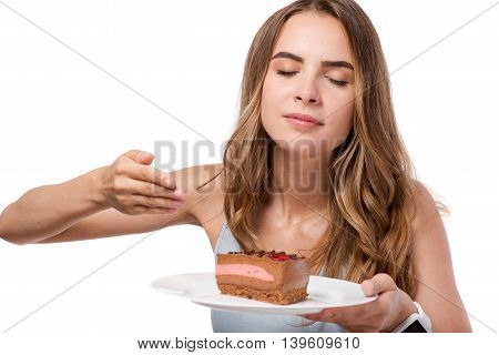 Delicious scent. Pleasant delighted woman holding plate with cake and smelling it while standing isolated on white background