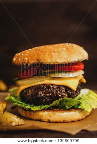 Grilled beef hamburger with vegetables on wood table