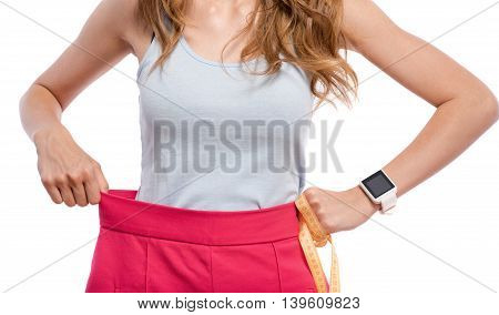Effective way of losing weight. Pleasant woman wearing her shorts and holding tape measure while standing isolated on white background