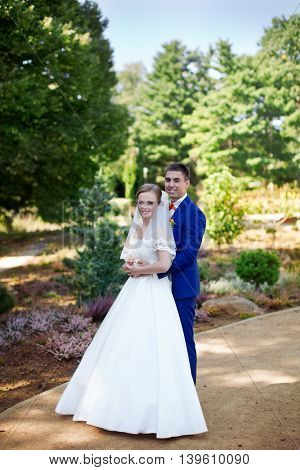 Funny bride and groom on a summer day in the park