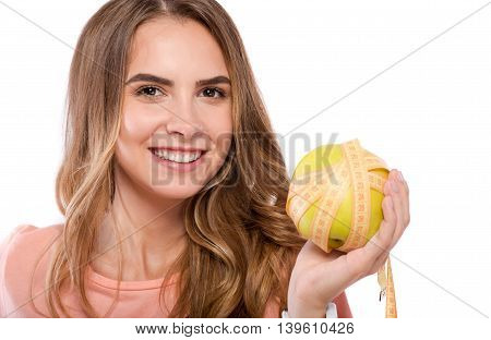 Full of energy. Portrait of cheerful nice woman smiling and holding apple while standing isolated on white background