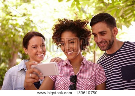 Three Young People Looking At A Cellphone
