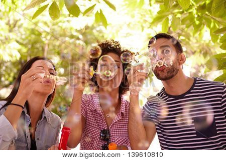 Three Joyful Young Friends Blowing Bubbles