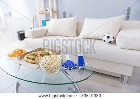 Everything ready for viewing football match. Cropped photo of living room with white sofa and pizza, chips, popcorn on coffee table