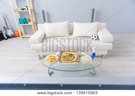 Everything organized correctly. White sofa standing in center of room in front of plasma near coffee table with pizza, chips, popcorn on coffee table