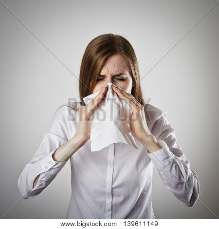 Young slim woman in white is sneezing.