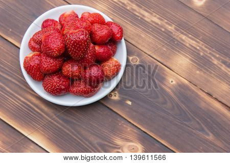Ripe strawberries in bowl on wooden table