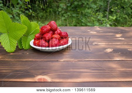 Fresh juicy strawberry isolated on a wooden table