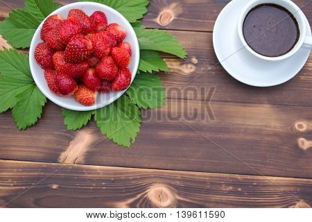 Ripe strawberries and a Cup of coffee on a wooden table