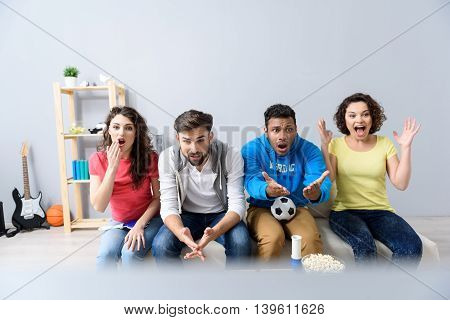 It is complex game. Four multi national friends supporting football team at home, sitting on sofa