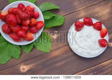 Strawberries and yoghurt in a bowl on wooden table close up