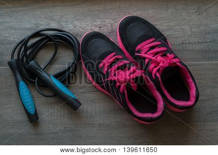 Pink sport shoes with jump rope on wooden background