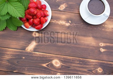 Strawberries and a Cup of coffee on a wooden table