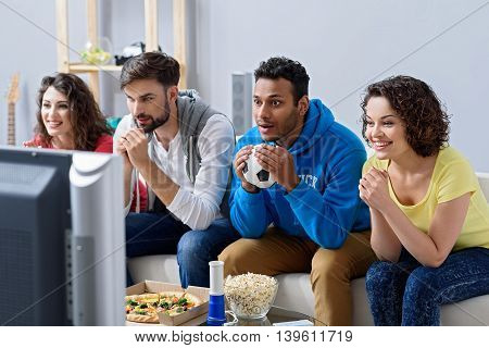 Real emotions unite friends. Sports friends fans cheering and celebrating exciting game on television, sitting on sofa at home