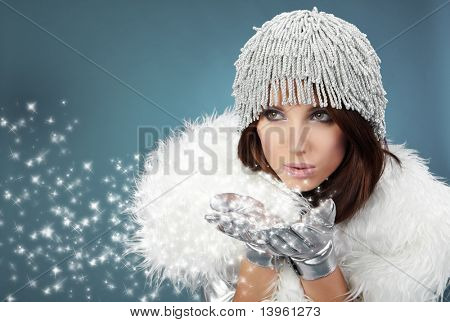 Attracive girl in santa cloth blowing snow from hands.