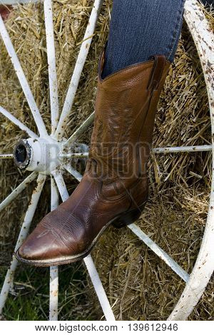 Cowgirl boot and wagon wheel on hay bale