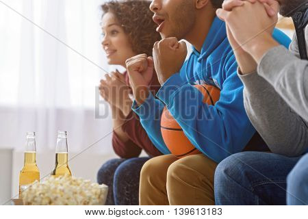 Let is score goal. Close up of worried group of basketball fans watching match, sitting in row on sofa at home