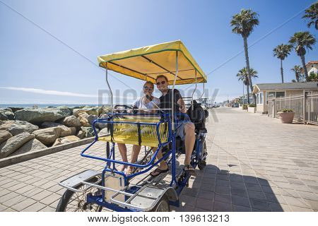 Couple riding a surrey bicycle or quadricycle together on a sunny day along the California coastline