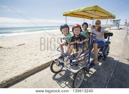 Family on a surrey bike ride along the coast of California