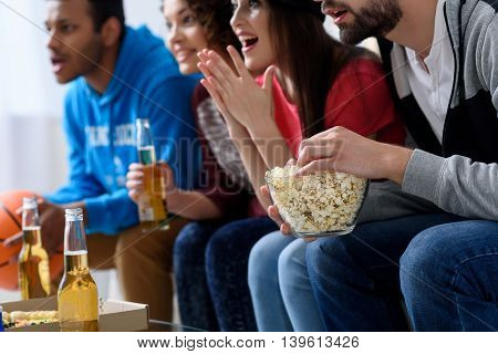 Score. Close up of happy fans watching sport tv and holding bottles of beer with popcorn, sitting at home