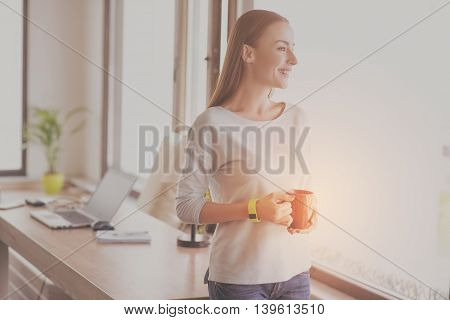 Nice working day. Happy and positive young woman drinking coffee and standing near window being in the office