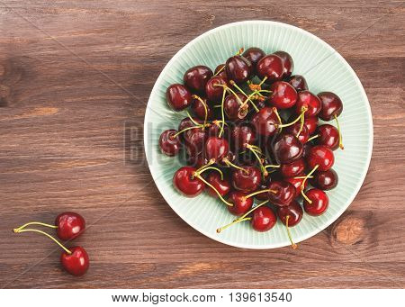 Plate of ripe cherries on a wooden rustic table