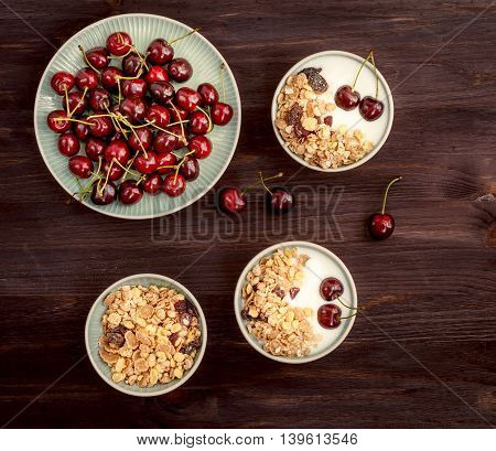Healthy breakfast with muesli, yogurt and ripe cherries on a wooden rustic table