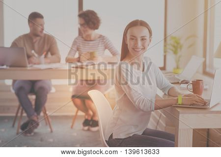 My workplace. Positive and optimistic young woman using laptop and her coworkers communicating in a background