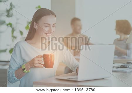 Busy one. Merry and positive young woman using laptop and holding cup of coffee with her coworkers in a background
