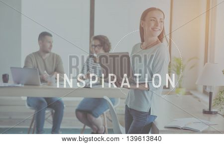 Develop your creativity. Inspirational typographic key message for inspiration with image of young smiling businesswoman holding laptop in a background