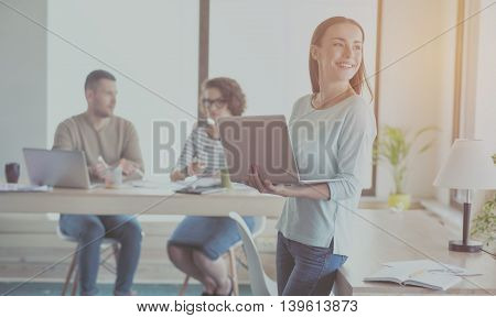 Like my work. Cheerful and delighted businesswoman holding laptop and using it with her colleagues communicating in a background