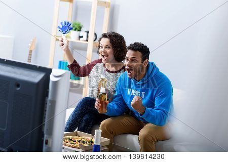 Having fun watching match. Shot of young woman and african man cheering on their favourite team, sitting on sofa at home