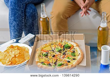 Very tasty and fragrantly. Top view of pizza and chips on table next to beer bottles with couple sitting on sofa in background