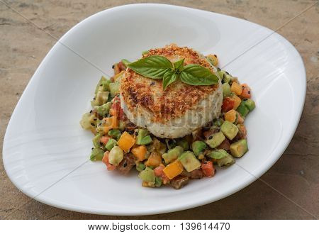 Homemade Crab Cake on a bed of Heirloom Tomato Salsa and Sesame Seed Chopped Avocado on a White Plate/ Selective Focus