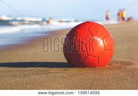 The red ball on the beach on the sand near the sea