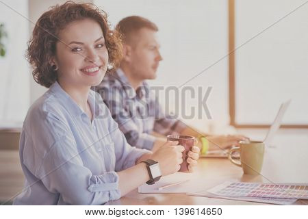 Confident woman. Happy and positive young businesswoman holding cup of coffee and smiling at a camera with her coworker using laptop in a background
