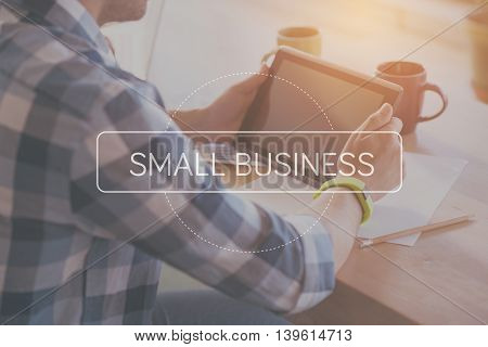 Working process detailed. Inspirational typographic poster for small business with cropped image of man using digital tablet in a background